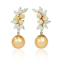 This pair of 18k white and yellow gold dangle earrings, feature 2 south sea golden pearls, a very high of luster, measuring 13mm in diameter with marquise cut white diamonds, weighing 2.68 carats total and fancy yellow diamonds, weighing 2.07 carats total
