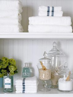 Shelving above tub with simple white towels and apothecary jars with bath salts and scoops, dried hydrangeas