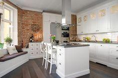 A Svédországban található konyha természetesen fa alapanyagokból készült, fehér színűre festve - így kiválóan mutat mellette a vörös téglafal és a sötét padlóburkolat.