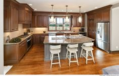 A welcoming kitchen features a large island, pantry and convenience accessories. Showplace Cabinetry extends to the family room, bathrooms, home bar, mudroom… Craftsman Style Decor, Large Windows, Mudroom, Countertops, Kitchen Remodel, Kitchen Design, Family Room, Table, Cabinets