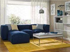 Salón con sofá azul y alfombra amarilla