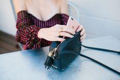 Blogger Lindsey Lutz from Life Lutzurious wearing a burgundy velvet off the shoulder top and Gigi New York bag