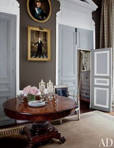 In the library of a Paris apartment designed by Jean-Louis Deniot, antique portraits by Joseph Combette (top) and the studio of Joseph Boze overlook a 19th-century French pedestal table; glimpsed through the doorway to the guest suite is an 1840s plaster Diana atop a Louis XVI-style semainier.