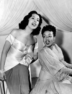 Lena Horne (standing) & Hazel Scott - Horne was a major international star of Broadway, television and motion pictures, who felt most at home singing nightclub jazz.  Schooled in piano at Juilliard, Scott created jazzy interpretations of classical music.