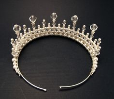 measures 2 1/4 inch at its highest point and contains Swarovski crystal, white glass pearls and cut crystal beads attached to a silver toned tiara band.