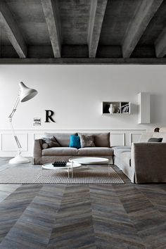 Sitting area with gray wood floors in a chevron pattern and concrete ceilings
