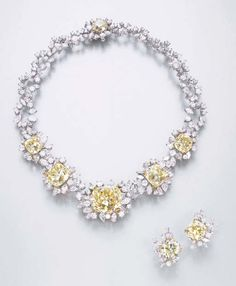 AN IMPORTANT SUITE OF FANCY YELLOW DIAMOND AND DIAMOND JEWELLERY, BY MEISTER  Comprising a necklace, designed as five graduated old mine-cut fancy yellow diamonds, the central diamond weighing approximately 42.54 carats, each within vari-cut diamond surrounds, to the scrolling backchain and fancy yellow diamond cluster clasp; and a pair of ear clips en suite, necklace 38.0 cm.  Signed EM for Meister
