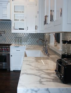 Bluish/ grayish Moroccan style tiles for the backsplash with Calcutta marble countertops   By MESA Designs (310) 955-6349