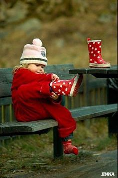 Little girl in red coat, putting on red polka-dotted rain boots. So sweet.