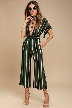 The Faithfull the Brand Cedric Green Striped Midi Jumpsuit always gets rave reviews! Lightweight woven fabric in a green, white, brown, and black striped pattern shapes a plunging V-neck and back and short sleeves. Banded waist with tying sash and side seam pockets top midi-length, culotte pants. Tying back with gold aglets and hidden back zipper/clasp.