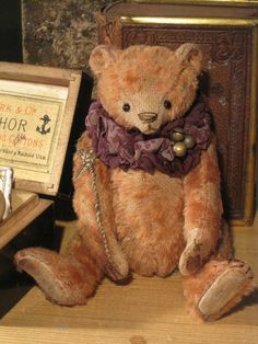 """The Old Post Office Bears, """"Troy"""" by Dawn Jellis-Jones, is a fully jointed bear made from genuine antique cinnamon German mohair.  He has linen paws, & joints that are heavy & loose giving him a well loved look. He is 5"""" from ear to paw, & has black glass eyes, a stitched nose, & is filled with polyester & heavily weighted with steel shot.  Troy has been distressed using various techniques to give him the look of an antique bear &, he comes with a pure silk ruff adorned with tiny brass…"""