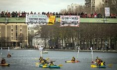 Indigenous people paddle down the Seine as others stand on a bridge holding banners during a rally in Paris demanding Indigenous rights are included in the climate accord on December 6, 2015 on the sidelines of the #COP21 climate change conference.