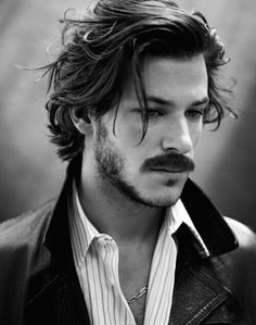 hairstyles for shoulder length hair, man with dark mustache and short beard, messy wavy hair brushed backwards, with a few loose strands on his face