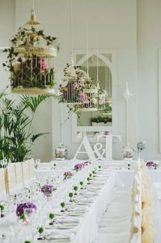 Simple and clean tablescape. Love the hanging birdcages full of flowers rather then having huge centerpieces. (captured by This Modern Love)