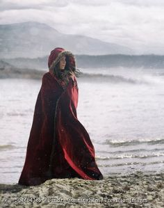 Trevillion Images - woman-in-red-cape-standing-near-the-water-with