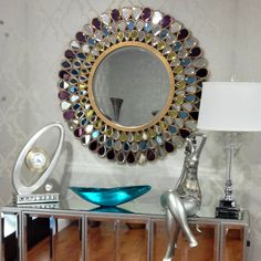 Gem Mirror elevates classic looks with sophisticated elegance. Donned in graduating circular rows of tear drop glass gems in hues of amethyst, amber, topaz and clear tear drop glass gems are embossed with exquisite gold detail Wood Framed Mirror, Diy Mirror, Beveled Mirror, Beveled Glass, Wall Mirrors, Mirror Makeover, Sunburst Mirror, Mirror Ideas, Wall Lamps