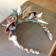 This enchanting Mermaid Seashell Crown is hand made with all natural seashells, and arranged together with blue painted Sea Stars, and tropical Combella shel