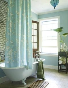 Porcelain claw foot tub, turquoise blue shower curtain, blue pendant light, koi fish vase, blue walls paint color and black bathroom cabinet.