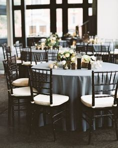 These table settings included slate-gray linens to accentuate the neutral color schemes and warm wood tones of the reception venue. See more of this South Carolina wedding by following the link