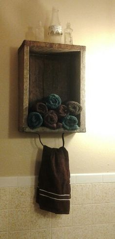 Old wooden box for hand towels. antique bottles on top for decor.