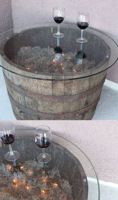 Cool patio table created from a whiskey barrel from Lowe's, round glass tabletop, spanish moss, and a string of lights. Really great outdoor patio decor idea.