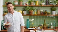 jamie's superfood - I love the green kitchen walls & tiles, set off with loads of plants and dark pink roses. Kitchen island is vintage wood library style drawers. Love it!