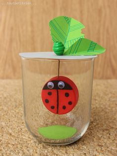 Coccinelle-bouchon suspendue dans un verre de Nutella, avec 2 ronds de papier vert et gris dans le fond et sur le dessus du verre. www.toutpetitrien.ch / fleurysylvie #bricolage #enfant