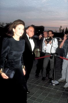 Jackie Onassis, accompanied by longtime companion Maurice Tempelsman, adapts '80s power-dressing to her own rigorous aesthetic in a Carolina Herrera evening dress with puffed shoulders and gold cuffs. 1988. - Photo: Brian Quigley/Time Life Pictures/Getty Images