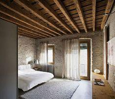 Chambre zen avec murs pierres et poutres apparentes