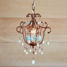 """BLUE RHAPSODY CHANDELIER--Working in the tradition of vintage European lighting, Meredith Clark ornaments a unique rusted iron chandelier frame with blue chalcedony. Handmade in the USA, each piece unique. 60w max. 36"""" hang cord."""