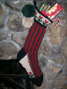 Old Fashioned Hand Knit Rustic Series Christmas Stocking From Santa's Stocking Works in a bold vertical stripe with flowers detail. This stocking has and Burgundy Red and Dark Sage Green body, with linen top and foot gusset back ground and black trim. These are are available for sale at http://www.etsy.com/shop/SantasSW and  www.santasstockingworks.com
