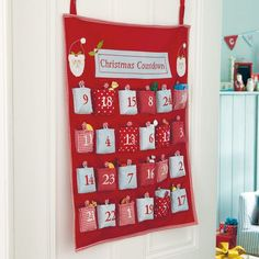 Christmas Countdown Fabric Advent Calendar - The whole family will love this advent calendar: you can hang it on a door, the 24 pockets are unusually roomy, and the numbers on the pockets are mixed up, so its still fun finding the right one! Its beautifully made with pretty, covered buttons and a mix of fabrics, along with embroidered numbers and applique Father Christmas designs.