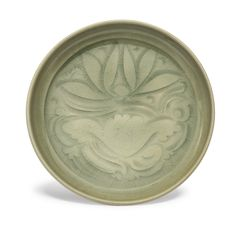A carved 'yaozhou' 'lotus' dish, Song dynasty,the shallow rounded sides supported on a short straight foot, freely carved to the interior with a medallion enclosing a lotus, covered overall in a rich olive-green glaze 13.8cm., 5 3/8 in.