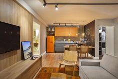 Cozinha integrada com a sala. Bancada cinza. Armário cinza e laranja (parte superior). Geladeira colorida. Mesa e cadeiras em madeira. Projeto:Andressa Fonseca