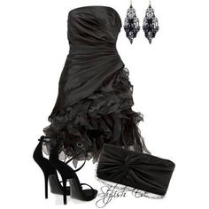 Medium length strapless black dress with side gather and runching and a tulle bottom on the flared skirt. With a black clutch and black strappy high heels, and dangly black chandelier earrings.