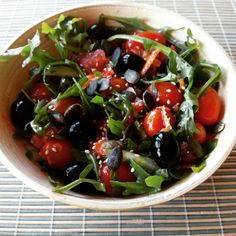 Ensalada de tomates cherry, pepino, rucula, aceitunas negras, semillas de calabaza y de sésamo.