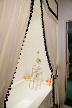 real window treatment style shower curtain with pelmet box and pom pom trim. Classic tile and hardware