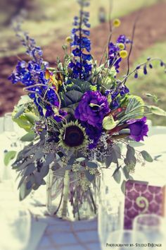 Rustic Meadow Wedding Centerpiece in blue, purple, green and yellow with~ billy buttons, blue delphinium, kale, purple lisianthus, sunflowers and eucalyptus