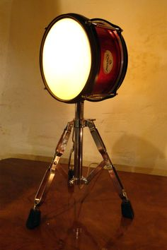 Drum stand (tripod) with old drum re-purposed to a standing lamp.
