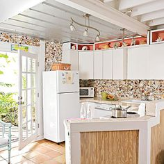 Hundreds of hand-placed shells form a textured backsplash and crafty wall art in this citrus-accented kitchen. | Coastalliving.com