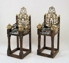 A Medieval chair or throne with an embroidered cushion of blue, silver and gold to ease the royal tush. Equally at home in a Gothic manor or castle, it could even be the chair of a sorcerer or witch. The frame is made of wood, with metal filigree forming the arms and adorning the back. Gold tone orbs finish the leg posts. I turned the front legs on a miniature lathe. The seat cushion is not removable. It measures 3 7/8 (9.8cm) tall x 1 1/2 (3.7cm) wide x 1 1/2 (3.6cm) deep. ...