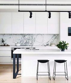Cozinha branca com mármore e bancos pretos