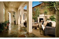 White stucco arches and a stone floor create an inviting courtyard focused on this outdoor fireplace. Residence 2 by Standard Pacific Homes. The Trailpoint Community. Walnut, CA.