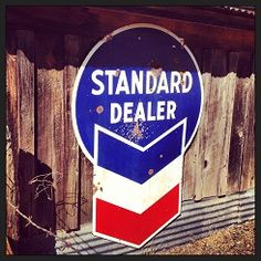 Standard Dealer tin sign on side of old gas station.