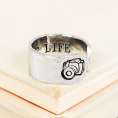 "This ""Capture Life"" aluminum ring is hand stamped with care, one letter at a time. The outside is textured and a Camera is stamped at the end. The rings are made out of Pure 1100 Aluminum, which is fo"