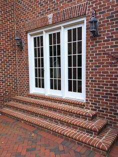 Enclosed in stately brick: Triple french doors exit to a paved brick patio.