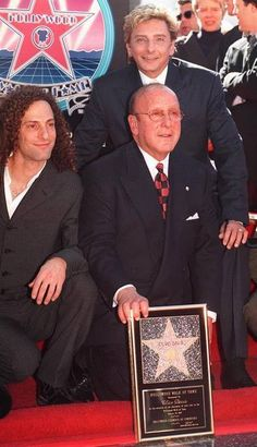 [PEOPLE DAVIS]Clive Davis, president of Arista Records, poses with Arista artists Kenny G, left, and Barry Manilow, background, as he receives a star on the Hollywood Walk of Fame Tuesday, Jan. 28, 1997. Davis is the first active record company president to receive the honor. (AP Photo/Chris Pizzello)