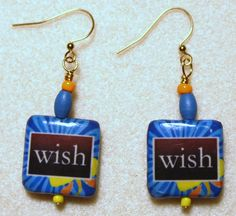 "Handcrafted by Teal Palmetto, LLC.  Make a wish!  Everyone should!  Square decoupaged ""wish"" beads in bright shades of orange, yellow, and blue are joined by wood and glass accent beads in the same colors.  They have gold fish hook ear wires. Price: $12."