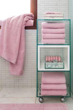 O carrinho em vidro ressalta a simplicidade do banheiro projetado pela arquiteta Lindamar Elias, além de organizar perfeitamente os itens essenciais de banho. A madeira dá sensação de calor e intimidade ao local, juntamente com as toalhas de tom quartzo.