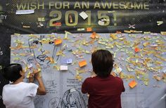 Onlookers write and post their New Year wishes on a wishing wall display at a mall in Quezon city, metro Manila December 31, 2014. The mall is gathering about 50,000 wishes, which will be used as confetti for its New Year celebrations alongside festive fireworks. (Photo by Romeo Ranoco/Reuters)